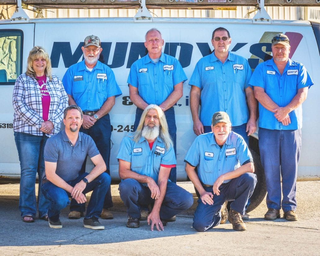 service techs and staff standing in front of a Mundy's van